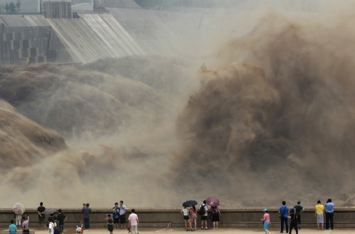 Local residents watch as sediment-laden flood water gushes through the Xiaolangdi Dam on the Yellow River in Luoyang